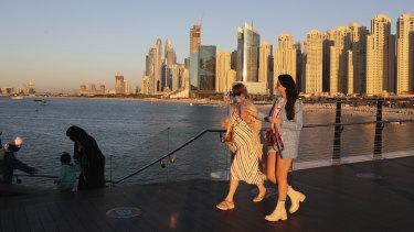 Tourists walk by an Emirati family in Dubai, United Arab Emirates.