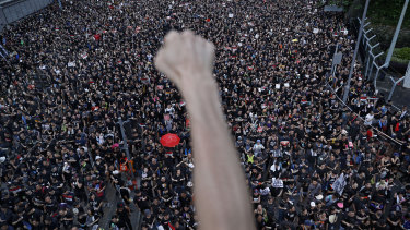 A protester clenches his fist as tens of thousands of protesters march on the streets to stage a protest against the unpopular extradition bill in Hong Kong.