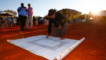 Noel Pearson signs the canvas for the Uluru Statement from the Heart.