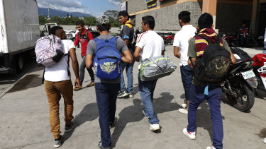 A group of young men arrive at a  bus station in San Pedro Sula, Honduras, to join scores of other migrants forming a caravan to travel to the US border on Monday.