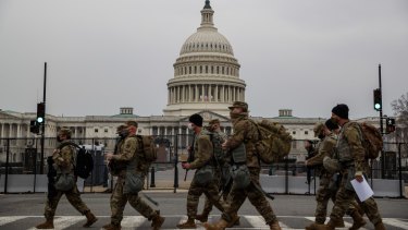 National Guard troops walk past the US Capitol building on the first day of hearings to impeach Donald Trump.