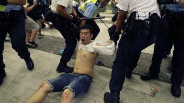 Police drag a protester away.