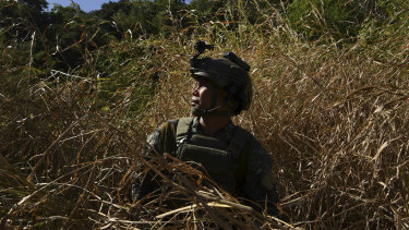 A marine special forces captain who fought in Marawi sits in the grass before training.