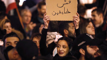 """An anti-government protester holds an Arabic placard that reads:""""We are not fearing"""" on Sunday."""