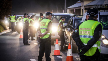 Police stop and question drivers arriving from Victoria at a checkpoint in Albury, NSW.