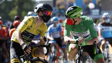 Britain's Adam Yates wearing the overall leader's yellow jersey speaks with Ireland's Sam Bennett, wearing the best sprinter's green jersey at the start of the sixth stage of the Tour de France.