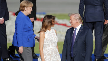 President Donald Trump, first lady Melania and German Chancellor Angela Merkel pose for a group photo of NATO leaders in Brussels.