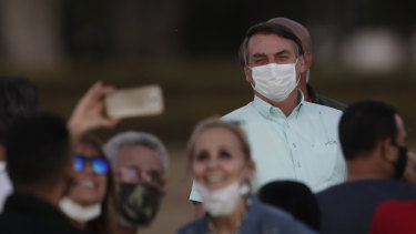 Supporters pose for a selfie with infected Brazilian President Jair Bolsonaro on Wednesday. Bolsonaro on the weekend said he has been cured.