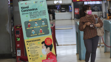 A woman passes an information banner on coronavirus at a train station in Jakarta, Indonesia.