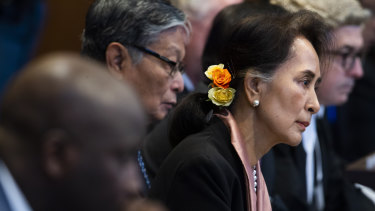 Myanmar's leader Aung San Suu Kyi and Gambia's Justice Minister Aboubacarr Tambadou, left, listen to judges in the court room.
