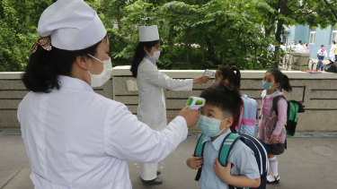 Students have their temperature checked in Seoul in June.