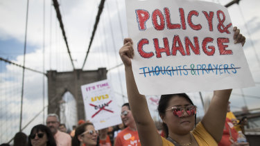 Demonstrators carry signs as they march over the Brooklyn bridge during a march and rally against gun violence.