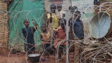 A displaced family stands behind the razor-wire that surrounds the United Nations' protected camp in Wau, South Sudan, in 2014.