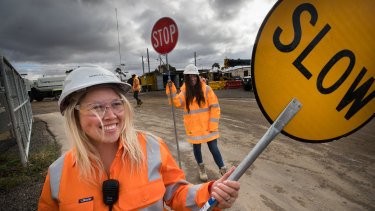 Rebecca Longo and Sherydan Fitzgerald direct traffic near a level crossing being constructed in Laverton, Victoria.