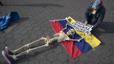 A supporter of Venezuelan opposition leader Juan Guaido secures a skeleton to a Venezuelan flag during a rally in New York's Union Square.