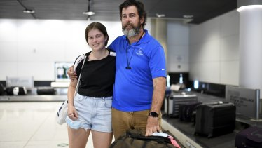 Simon Davis and his daughter Amelie, frustrated after missing a family Christmas, arrive at Brisbane Airport from Wollongong via Sydney on Monday.
