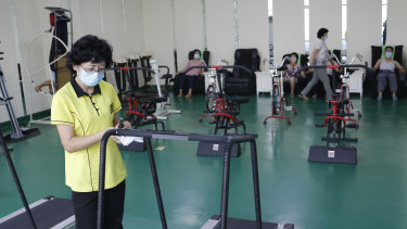 An employee disinfects a treadmill at the Ryugyong Health Complex in Pyongyang, North Korea.