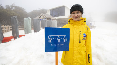 A Mt Buller ski services staff member displays the social-distancing measures the resort was using on its ski lifts.