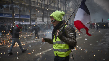 A Gilet Jaune, or Yellow Vest, holds a French Tricolor amidst tear gas as protesters and French Riot Police clash during a rally near Place de Republique on Thursday.