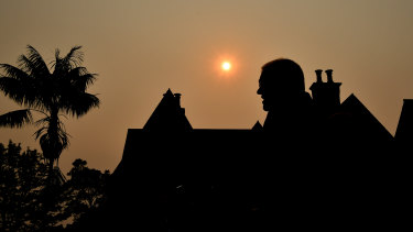 Scott Morrison silhouetted by a smoky sunset over Kirribilli this month.