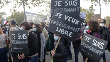 "Demonstrators hold placards reading ""I am a teacher"" and ""I want a free teacher"" in Paris on Sunday."