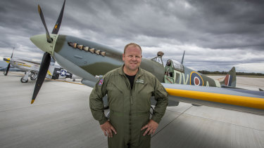 Spitfire pilot Cameron Rolph-Smith poses in front of a restored Spitfire on Brisbane's new runway.