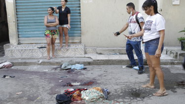Residents take pictures of blood on the street after the shoot-out in the Jacarezinho favela.
