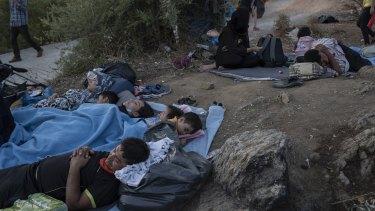Migrants sleep outside the burned Moria refugee camp.
