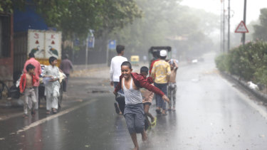 A boys runs in the middle of a street as others play during a sudden rain and dust storm amid India's lockdown in Delhi, India.