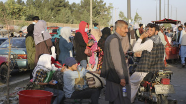 Hundreds of people gather near an evacuation control checkpoint during ongoing evacuations at Hamid Karzai International Airport, in Kabul, Afghanistan.