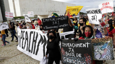 """Demonstrators shout """"Bolsonaro Out"""" and carry signs written in Portuguese calling for the impeachment of Brazilian President Jair Bolsonaro impeachment in Brasilia on Sunday."""