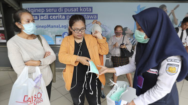 Train officers distributed protective face masks to passengers at a train station in Jakarta, Indonesia.