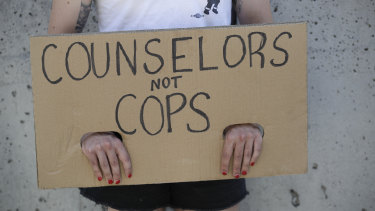 A demonstrator holds a sign during a protest in Los Angeles, where parents, students, and teachers held a press conference and car caravan to call for a safe, fully funded, and racially just approach to reopening schools.