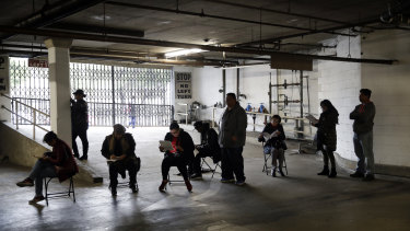 Hospitality workers wait in line in a basement garage to apply for unemployment benefits in Los Angeles.