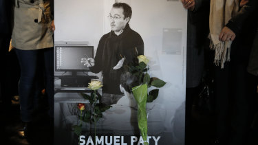 People hold a photo of the history teacher Samuel Paty during a memorial march in Conflans-Sainte-Honorine, north-west of Paris.