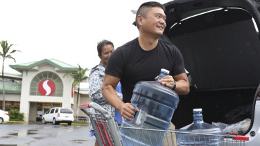 Loren, right, and Ruby Aquino, of Honolulu, load water into their car ahead of Hurricane Lane in Honolulu.
