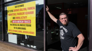 Anthony Rachelle with the sign he has put on his store.