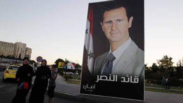 "A poster of President Bashar al-Assad with Arabic that reads, ""Leader of the victory,"" hangs on a street at Omayyid Square, Syria."
