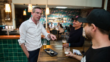 NSW Treasurer Dominic Perrottet has a beer at The Balmain Hotel with owner Justin Small as restrictions were eased on bars and pubs on Friday.