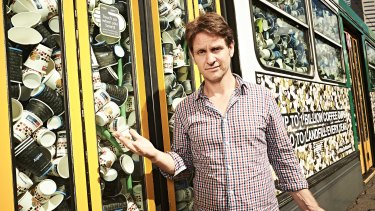 War on Waste presenter Craig Reucassel with a Melbourne tram stuffed with more than 50,000 takeaway coffee cups - representing what Australians send to landfill every half-hour.