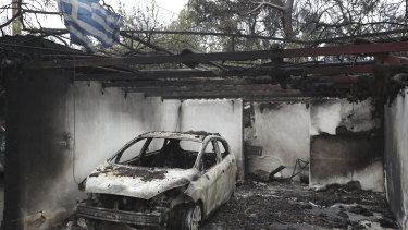 A Greek national flag flutters over the charred remains of a burned-out car and house in Mati.
