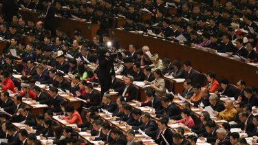 Delegates from all walks of life listen to the Government Work Report delivered by Li at the People's Congress in Beijing.