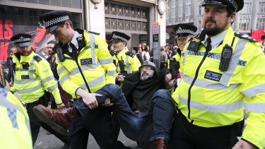 Police officers carry a protester away at Oxford Circus in London on Wednesday.