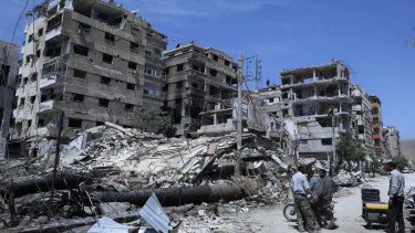 People stand in front of damaged buildings, in the town of Douma.