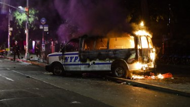 A Police vehicle burns after protesters rallied in New York on Friday over the death of George Floyd, a black man who died in Minneapolis police custody