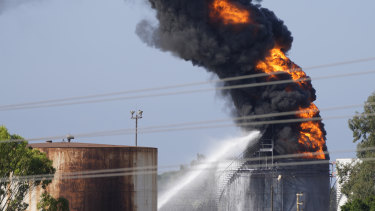 Firefighters work to extinguish a fire in an oil facility in the southern Lebanese town of Zahrani.