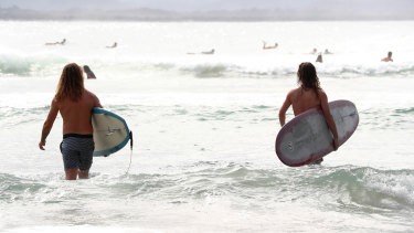 Surfers with and without a leg rope at The Pass in Byron Bay.
