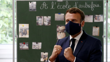 Fighting spirit: President Emmanuel Macron, wearing the new 100 per cent French face mask, speaks with children during class at the Pierre Ronsard elementary school on Tuesday.