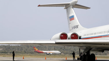 A Chinese plane lands near a Russian plane parked on the tarmac at the Simon Bolivar International Airport in Maiquetia, near Caracas, Venezuela.