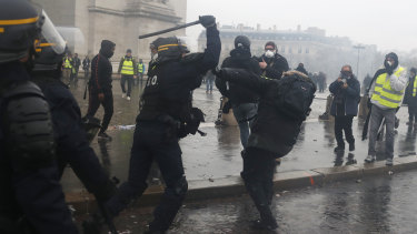A riot police officer uses his baton on a demonstrator during a demonstration at the Arc de Triomphe.